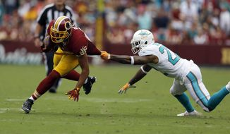 Washington Redskins tight end Jordan Reed (86) is tackled by his jersey by Miami Dolphins cornerback Jamar Taylor (22) during the first half of an NFL football game Sunday, Sept. 13, 2015, in Landover, Md. (AP Photo/Patrick Semansky)