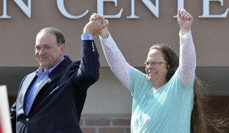 In this Tuesday, Sept. 8, 2015, file photo, Rowan County Clerk Kim Davis, with Republican presidential candidate Mike Huckabee at her side, greets the crowd after being released from the Carter County Detention Center, in Grayson, Ky. (AP Photo/Timothy D. Easley, File)