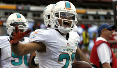 Miami Dolphins cornerback Brent Grimes (21) celebrates his interception during the first half of an NFL football game against the Washington Redskins, Sunday, Sept. 13, 2015, in Landover, Md. (AP Photo/Evan Vucci)