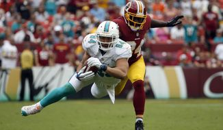 Miami Dolphins tight end Jordan Cameron (84) catches a pass for a first down in front of Washington Redskins free safety Trenton Robinson (34) during the second half of an NFL football game Sunday, Sept. 13, 2015, in Landover, Md. (AP Photo/Evan Vucci)