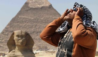An Egyptian uses special glasses to view a partial solar eclipse as people gather near the Sphinx at the Giza Pyramids on the outskirts of Cairo, Egypt, on March 20, 2015. (Associated Press)