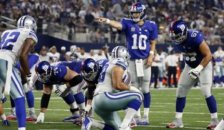 In this photo taken Sunday, Sept. 13, 2015, New York Giants quarterback Eli Manning (10) calls out at the line of scrimmage during the second half of an NFL football game against the Dallas Cowboys in Arlington, Texas. New York was about to put a damper on another festive prime-time opener Sunday night. Instead, the Giants were stunned 27-26 on a winning drive by Tony Romo after Manning admittedly made a crucial mistake.  (AP Photo/Tony Gutierrez)