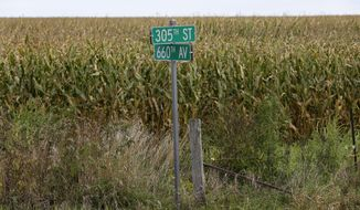 This Tuesday, Sept. 8, 2015 photo shows a street sign in front of a corn field at an uncontrolled rural intersection where a driver was killed in an August crash near Maxwell, Iowa. Corn grows up to 12 feet tall and this time of year can be a serious hazard for motorists in rural areas of the Midwest. (AP Photo/Charlie Neibergall)