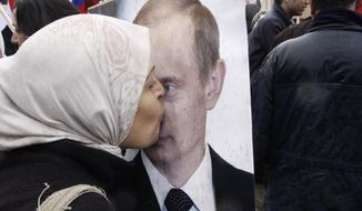A Syrian woman kisses a poster of Russian President Vladimir Putin during a pro-Syrian government protest in front of the Russian Embassy in Damascus, Syria. (AP Photo/Muzaffar Salman, File)