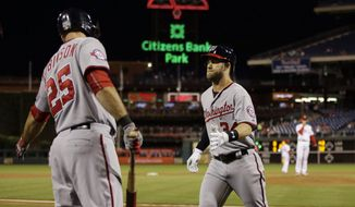 Washington Nationals' Bryce Harper, center, celebrates with Clint Robinson, left, after Harper hit a home run off Philadelphia Phillies starting pitcher Aaron Nola, right, during the third inning of a baseball game, Monday, Sept. 14, 2015, in Philadelphia. (AP Photo/Matt Slocum)