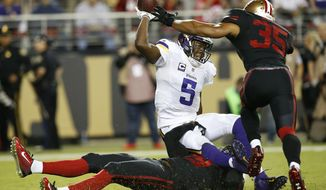 Minnesota Vikings quarterback Teddy Bridgewater (5) is sacked by San Francisco 49ers strong safety Jaquiski Tartt, bottom, as safety Eric Reid (35) follows during the first half of an NFL football game in Santa Clara, Calif., Monday, Sept. 14, 2015. (AP Photo/Tony Avelar)