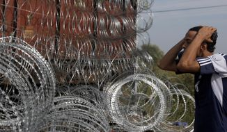 A migrant looks and reacts at the closed railway border crossing between Serbia and Hungary, near Horgos, Serbia, Tuesday, Sept. 15, 2015. Hungary has declared a state of emergency in two of its southern counties bordering Serbia because of the migration crisis, giving special powers to police and other authorities. (AP Photo/Darko Vojinovic)