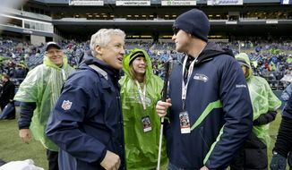 Seattle Seahawks head coach Pete Carroll, left, talks with Jake Olson, 16, before an NFC divisional playoff NFL football game against the New Orleans Saints in Seattle, Saturday, Jan. 11, 2014. (AP Photo/Elaine Thompson)