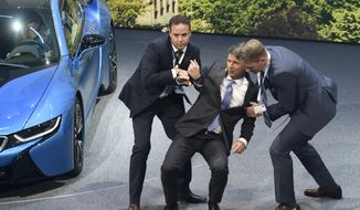 BMW CEO Harald Krueger, center, is helped to his feet after collapsing during the BMW presentation on the first press day of the Frankfurt Auto Show IAA in Frankfurt, Germany, Tuesday, Sept. 15, 2015. The car show runs through Sept. 27. (AP Photo/Jens Meyer)