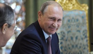 Russian President Vladimir Putin smiles as he listens to Russia's Foreign Minister Sergey Lavrov, left, at the meeting of the Collective Security Treaty Organization (CSTO) in Dushanbe, Tajikistan, Tuesday, Sept. 15, 2015. Russian President Vladimir Putin on Tuesday strongly defended Moscow's military assistance to the Syrian government, saying it's impossible to defeat the Islamic State group without cooperating with the Syrian government. (Mikhail Klimentyev/RIA-Novosti, Kremlin Pool Photo via AP) ** FILE **