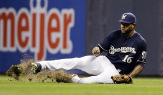 Milwaukee Brewers' Domingo Santana makes a sliding catch on a ball hit by St. Louis Cardinals' Jhonny Peralta during the fifth inning of a baseball game Wednesday, Sept. 16, 2015, in Milwaukee. (AP Photo/Morry Gash)