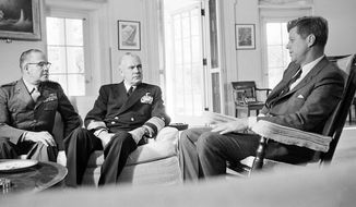 In this Oct. 29, 1962, photo, President John F. Kennedy poses in the White House office with Gen. David Shoup, left, Marine Corps Commandant, and Adm. George Anderson, Chief of U.S. Naval Operations in Washington. The chiefs met with the president to review the situation in Cuba and operation of the U.S. naval blockade.  As the U.S. and Russia reached the brink of nuclear war in 1962, Kennedy received top-secret intelligence from the CIA that a new warhead launcher was spotted in Cuba. That report, given to Kennedy a day before the end of the Cuban Missile Crisis, is among roughly 19,000 pages of newly declassified CIA documents from the Cold War released Wednesday, Sept. 16, 2015. (AP Photo/William J. Smith, File)