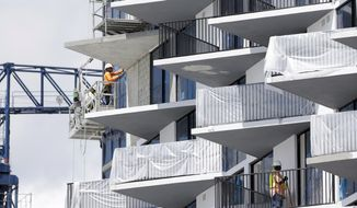 Construction workers labor at the site of a high-rise condominium that is part of the downtown Doral complex developed by the Codina Partners in Doral, Fla., in this Monday, Aug. 17, 2015, file photo. The National Association of Home Builders/Wells Fargo released its September index of builder sentiment on Wednesday, Sept. 16, 2015. (AP Photo/Lynne Sladky)