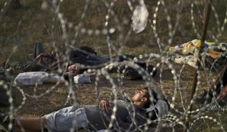 Afghan refugees sleep next to razor-wire barrier at the Serbian side of Hungary's border fence with Serbia, in Asotthalom, southern Hungary, Thursday, Sept. 17, 2015. Thousands of migrants have begun pouring into Croatia, setting up a new path toward Western Europe after Hungary used tear gas and water cannons to keep them out of its territory. (AP Photo/Muhammed Muheisen)