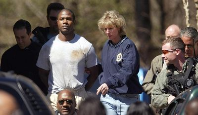 """FILE - In this March 12, 2005 file photo, murder suspect Brian Nichols is led by an unidentified officer at the FBI office in Atlanta. Nichols, accused of killing a judge and two other people at an Atlanta courthouse, was captured at a suburban Atlanta apartment complex hours after an federal immigration agent was discovered shot to death miles away. Actor David Oyelowo portrays Nichols in the film, """"Captive,"""" which opens nationwide on Friday.   (AP Photo/John Bazemore, File)"""