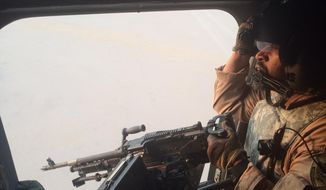 An Emirati gunner aboard a Chinook military helicopter scans the desert over Yemen on Wednesday, Sept. 16, 2015. The Emiratis are part of thousands of Saudi Arabia and UAE forces fighting on the ground in Yemen to reverse the territorial gains by the Iran-backed rebels known as Houthis, who captured Sanaa last year and much of the country's north. (AP Photo/Adam Schreck)