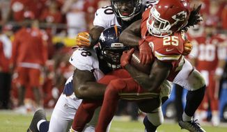 Kansas City Chiefs running back Jamaal Charles (25) is tackled by Denver Broncos nose tackle Darius Kilgo (98) and safety David Bruton Jr. (30) during the second half of an NFL football game in Kansas City, Mo., Thursday, Sept. 17, 2015. (AP Photo/Charlie Riedel)