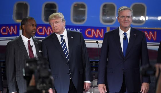 Republican presidential candidates (from left) Ben Carson, Donald Trump and former Florida Gov. Jeb Bush pose for a group picture during the CNN Republican presidential debate at the Ronald Reagan Presidential Library and Museum in Simi Valley, Calif., on Sept. 16, 2015. (Associated Press)