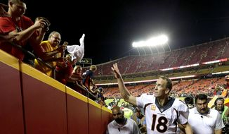 Denver Broncos quarterback Peyton Manning (18) tosses a towel to fans after the Broncos' NFL football game against the Kansas City Chiefs on Thursday, Sept. 17, 2015, in Kansas City, Mo. The Broncos won 31-24. (AP Photo/Charlie Riedel)