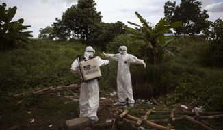 ADVANCE FOR USE SUNDAY, SEPT. 20, 2015 AT 9 P.M. EDT (0100 GMT) AND THEREAFTER - FILE - In this Wednesday, Sept. 24, 2014 file photo, a health worker sprays a colleague with disinfectant after working inside a morgue with people suspected of dying from the Ebola virus, in Kenema, eastern Sierra Leone. An Associated Press investigation has found that the World Health Organization and other responders faced key obstacles in their efforts to stop the spiraling Ebola outbreak in the summer of 2014 in Kenema, a pivotal seeding point for the virus and a microcosm of the messy response across West Africa. (AP Photo/Tanya Bindra, File)