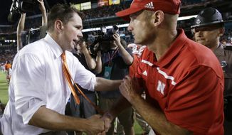Miami head coach Al Golden, left, and Nebraska head coach Mike Riley congratulate each other after Miami defeated Nebraska 36-33 in an overtime period of an NCAA college football game, Saturday, Sept. 19, 2015 in Miami Gardens, Fla. (AP Photo/Wilfredo Lee)