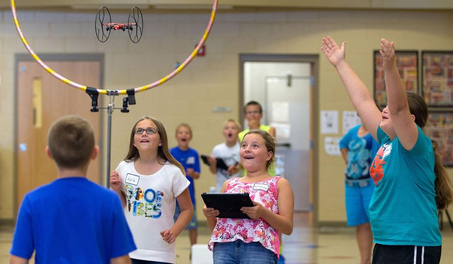 FOR RELEASE SATURDAY, SEPTEMBER 19, 2015, AT 12:01 A.M. CDT - In this Aug. 25 photo, fifth-grade students Kyla Paladino, Katherine Vandenberg and Sophie English react as their drone flies through a hula hoop during an experiment at Whitetail Elementary in Gretna, Neb. (Megan Farmer/Omaha World-Herald via AP) MAGS OUT; ALL NEBRASKA LOCAL BROADCAST TELEVISION OUT; MANDATORY CREDIT