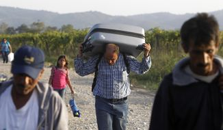 A Syrian refugee carries a suitcase on his shoulders along a dusty road, after entering from Greece into Macedonia, near the southern Macedonian town of Gevgelija, on Saturday, Sept. 19, 2015. About 5,000 migrants and refugees are transiting average daily through the transit camp at Macedonia's town of Gevgelija, on their way to Serbia and more prosperous European countries. (AP Photo/Boris Grdanoski)