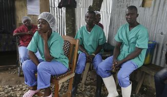 In this Monday, Aug. 10, 2015, photo, health workers take a break at the Kenema Government Hospital, where more than 40 health workers died of Ebola, in Kenema, eastern Sierra Leone. (AP Photo/Sunday Alamba)