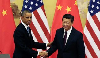 FILE - In this Nov. 12, 2014 file photo, U.S. President Barack Obama, left, shakes hands with his Chinese counterpart Xi Jinping after their press conference at the Great Hall of the People in Beijing, China. (AP Photo/Andy Wong, File)