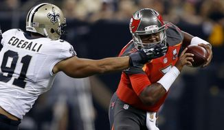 Tampa Bay Buccaneers quarterback Jameis Winston (3) scrambles under pressure from New Orleans Saints outside linebacker Kasim Edebali (91) in the first half of an NFL football game in New Orleans, Sunday, Sept. 20, 2015. (AP Photo/Jonathan Bachman)