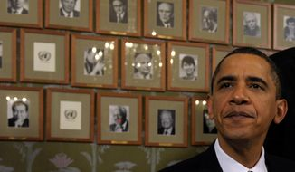 President Obama sits in front of framed photos of previous Nobel Peace Prize winners during a signing ceremony at the Norwegian Nobel Institute in Oslo on Dec. 10, 2009. (Associated Press)