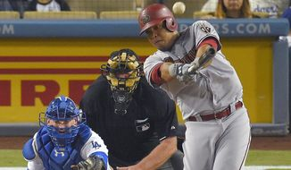 Arizona Diamondbacks' Yasmany Tomas, right, hits a solo home run as Los Angeles Dodgers catcher Yasmani Grandal, left, watches along with home plate umpire Bob Davidson during the fourth inning of a baseball game, Monday, Sept. 21, 2015, in Los Angeles. (AP Photo/Mark J. Terrill)