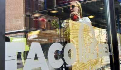 A customer at the new Taco Bell Cantina restaurant tries out Twisted Freeze, mixed drink, Tuesday, Sept. 22, 2015, in Chicago. The chain, which is owned by Yum Brands Inc., opened the location that serves wine, beer, sangria and frozen mixed drinks in Chicago. (AP Photo/Matt Marton) ** FILE **