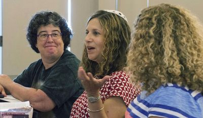 In this Sept. 5, 2015 photo, interim Rabbi Rebecca L. Dubowe speaks to a group during a Torah reading and Bible study at the Moses Montefiore Temple in Bloomington, Ill. Temple member Cathie Marx of Normal is at left, while Rabbi Dubowe's daughter, Arielle Dubowe of Los Angeles, California, is at right. (Steve Smedley/The Pantagraph via AP)