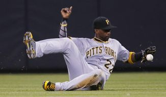 Pittsburgh Pirates center fielder Andrew McCutchen tries to catch a single off the bat of Colorado Rockies' Jose Reyes in the fourth inning of a baseball game Monday, Sept. 21, 2015, in Denver. (AP Photo/David Zalubowski)