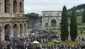 Tourists crowd the Colosseum in spite of the bad weather in Rome Sunday, April 5, 2015. Intermittent rains did not prevent tourists to visit the ancient remains during the Easter weekend. (AP Photo/Alessandro Di Meo, ANSA)