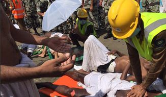 In this image posted on the official Twitter account of the directorate of the Saudi Civil Defense agency, a pilgrim is treated by a medic after a stampede that killed and injured pilgrims in the holy city of Mina during the annual hajj pilgrimage on Thursday, Sept. 24, 2015. (Directorate of the Saudi Civil Defense agency via AP)