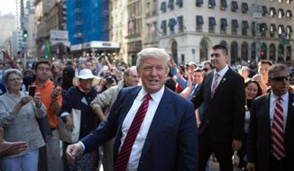U.S. Presidential Candidate Donald Trump greets the crowd gathered in front of the Trump Tower ahead of the arrival of the pope's motorcade Thursday, Sept. 24, 2015, in New York.  (AP Photo/Kevin Hagen) ** FILE **