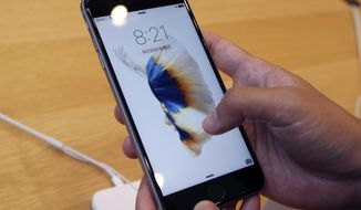 A customer tries new iPhone 6s on display at an Apple store in Tokyo Friday, Sept. 25, 2015. Apple is counting on sales of the new iPhones to maintain its position as one of the most profitable, and valuable, companies in the world. (AP Photo/Koji Sasahara)
