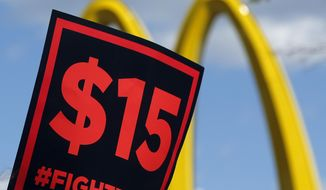 In this July 22, 2015, file photo, supporters of a $15 minimum wage for fast-food workers rally in front of a McDonald's in Albany, N.Y. (AP Photo/Mike Groll, File)