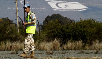 FILE - In this Tuesday, Feb. 11, 2014 file photo, an Argentinean UN peacekeeper stands guard in front of the painted Turkish flag, left, and the Turkish Cypriot breakaway flag on Pentadaktilos mountain in the Turkish occupied in northern Cyprus. Suicide bombings, improvised explosive devices and combatants with little regard for the rules of war are making the work of nearly 125,000 U.N. peacekeepers look more and more like counterterrorism operations. Some U.N. member states balk at sending their troops into such conditions to protect civilians. Others ask how heavily armored U.N. troops can promote peace. And new allegations of sexual abuses by U.N. peacekeepers expose deep gaps in training and accountability. (AP Photo/Petros Karadjias, File)