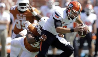 Oklahoma State's Mason Rudolph, right, is pressured by Texas's Bryce Cottrell (91) during the first half of an NCAA college football game, Saturday, Sept. 26, 2015, in Austin, Texas. (AP Photo/Eric Gay)
