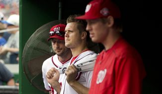 From left to right, Washington Nationals pitchers Max Scherzer, Jonathan Papelbon and Stephen Strasburg watch the eighth inning of a baseball game against the Philadelphia Phillies at Nationals Park in Washington, Sunday, Sept. 27, 2015, after Papelbon got into a dugout fight with teammate Bryce Harper during the inning. The Phillies won 12-5. (AP Photo/Jacquelyn Martin)