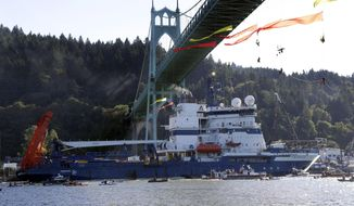 In this July 30, 2015 file photo, the Royal Dutch Shell PLC icebreaker Fennica heads up the Willamette River under protesters hanging from the St. Johns Bridge on its way to Alaska in Portland, Ore.  Royal Dutch Shell will cease exploration in Arctic waters off Alaska's coast following disappointing results from an exploratory well backed by billions in investment and years of work. (AP Photo/Don Ryan, File)
