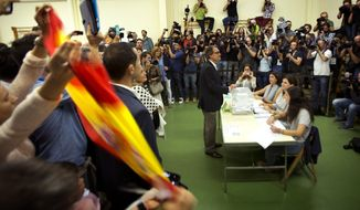 A Spanish flag is held up as the President of Democratic Convergence of Catalonia Artur Mas, center, votes at a polling station in Barcelona, Spain, Sunday Sept. 27, 2015. Voters in Catalonia participated in an election Sunday that could propel the northeastern region toward independence from the rest of Spain or quell secessionism for years. (AP Photo/Emilio Morenatti)