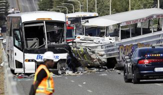 "An emergency official stands near a charter bus, left, and a ""Ride the Ducks"" amphibious tour bus following a fatal crash that killed five people Thursday, Sept. 24, 2015, in Seattle. The duck boat did not have an axle repair that was recommended for at least some of the amphibious tour vehicles in 2013, federal investigators said.(AP Photo/Ted S. Warren)"