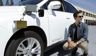 In this Monday, Aug. 24, 2015, file photo, Brian Torcellini, Google team leader of driving operations, poses for photos next to a self-driving car at a Google office in Mountain View, Calif. (AP Photo/Jeff Chiu)