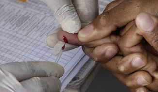 """In this Monday, Nov. 29, 2010, file photo a patient undergoes a blood test inside a mobile health care clinic parked in downtown Johannesburg. Passersby are encouraged to volunteer to be tested for the HIV virus in a """"Know Your Status"""" government drive. The World Health Organization has revised its HIV guidelines to recommend that anyone who tests positive for the virus that causes AIDS should be treated immediately. (AP Photo/Denis Farrell, File)"""