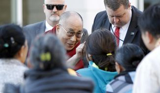 The Dalai Lama greets members of Minnesota Tibetan community upon arrival to the Mayo Civic Center, Wednesday, Sept. 30, 2015, in Rochester, Minn., following his stay at the Mayo Clinic. (Elizabeth Nida Obert/The Rochester Post-Bulletin via AP) MANDATORY CREDIT