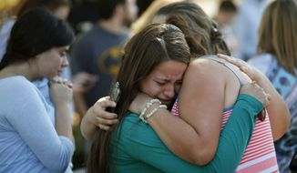 Jessica Vazquez (left) hugs her aunt, Leticia Acaraz, as they await word on Acaraz's daughter after a deadly shooting at Umpqua Community College, in Roseburg, Ore., on Thursday, Oct. 1, 2015. (The Register-Guard via Associated Press)